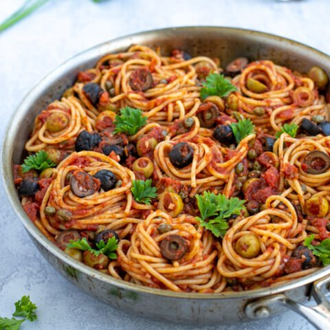 skillet on a table full of puttanesca pasta garnished with olives and parsley
