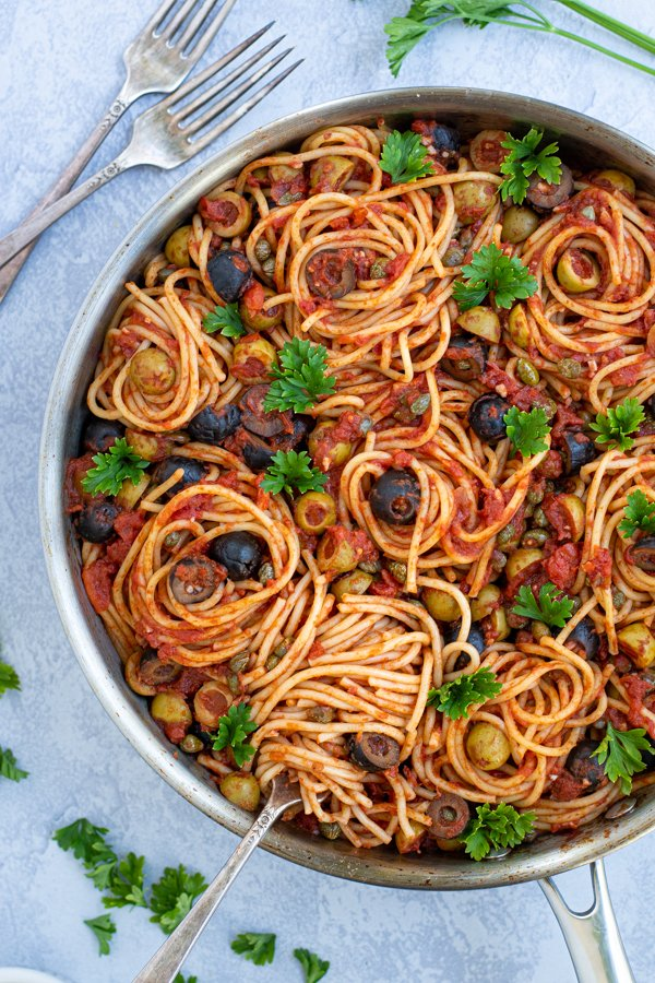 a fork spiraling some spaghetti puttanesca in a large skillet garnished by parsley
