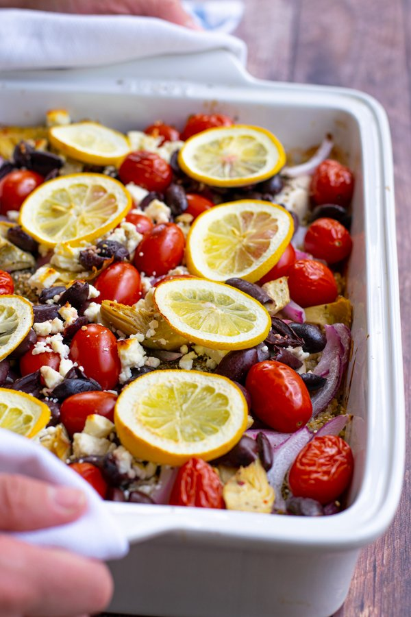 hand holding a baking dish with one pan greek chicken bake