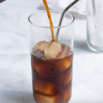 Pinterest Pin for how to make cold brew coffee show a photo of cold brew concentrate being poured into a glass of ice