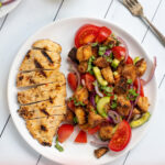 Pinterest Pin for Grilled Chicken Panzanella Salad showing a white plate with a grilled chicken breast and a pile of panzanella salad