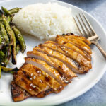 Pinterest Pin showing a grilled chicken breast sliced up on a plate net to grilled green beans