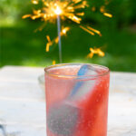 Pinterest Pin for red, white, and blue ice cubes showing a drink with patriotic ice cubes outside next to a sparkler