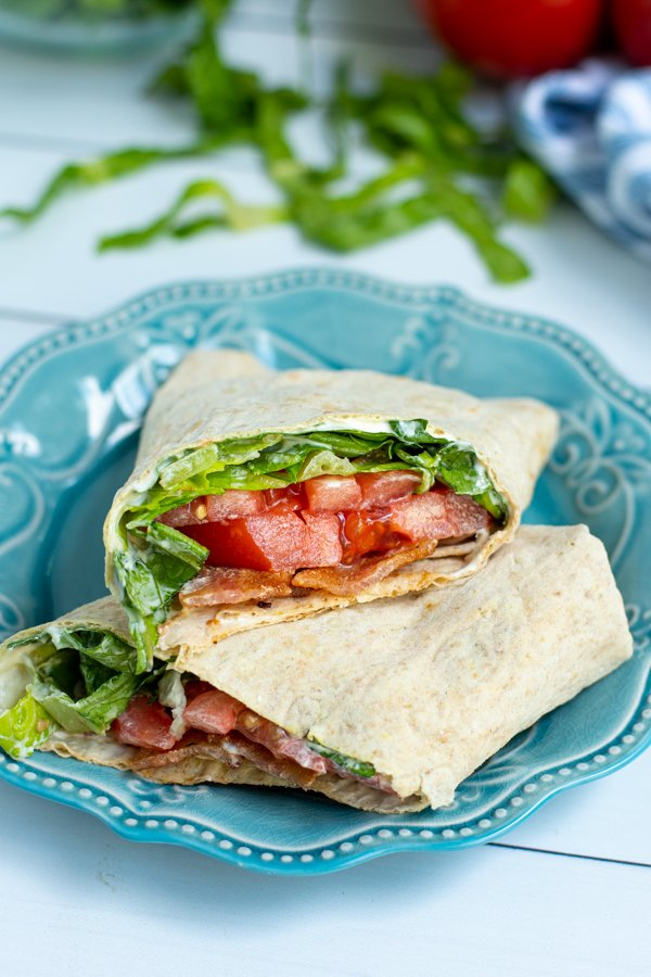 a BLT wrap sliced in half showing the ingredients on a blue plate