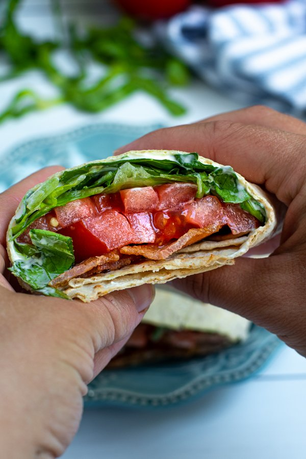 a cut half of a BLT wrap in a pair of hands showing off the bacon, lettuce, and tomato on the inside
