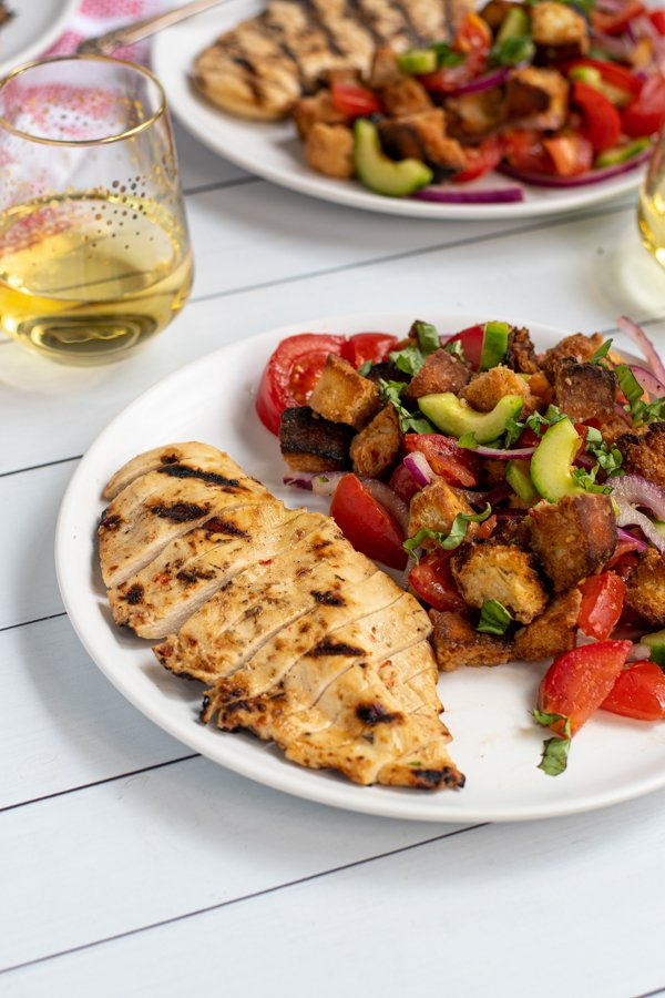 grilled chicken sliced up on a plate next to a large serving of panzanella salad with grilled bread