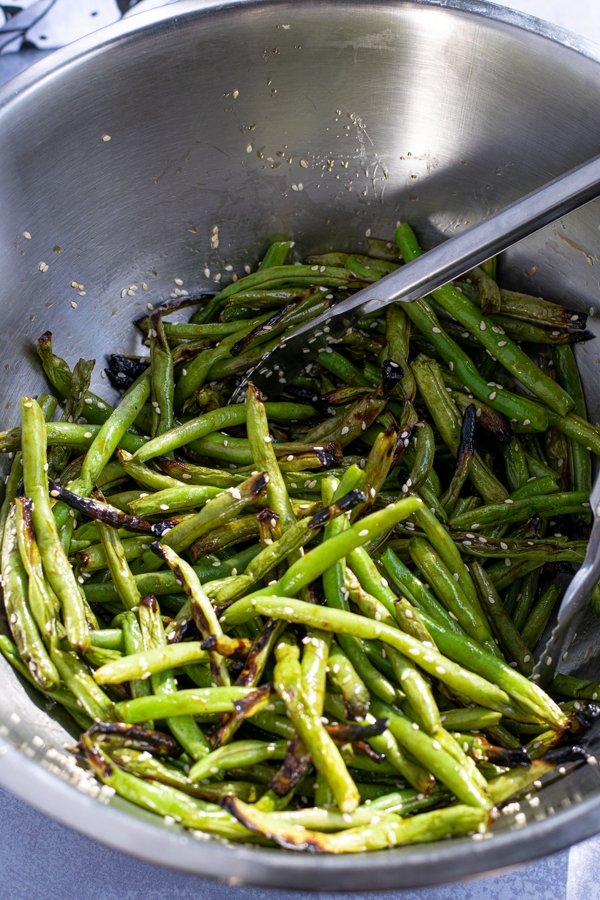 grilled green beans in a large bowl with tongs tossed in teriyaki sauce and sesame seeds