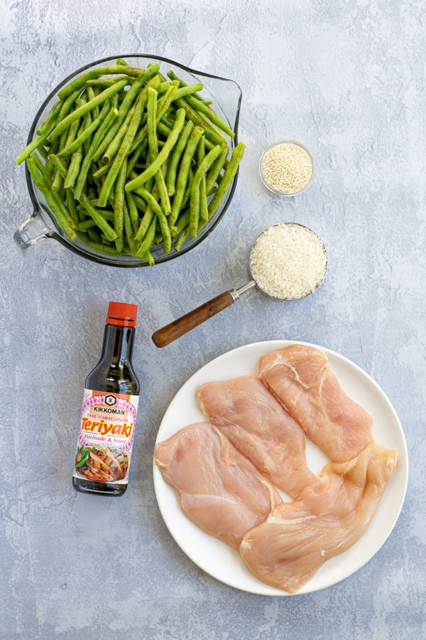 flatly showing the five ingredients needed for the recipe, chicken breast, teriyaki sauce, white rice, green beans, and sesame seeds