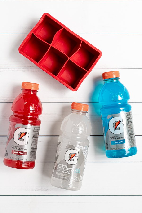 red, white, and blue gatorades laying next to a large ice cube tray, everything you need to make colorful ice cubes