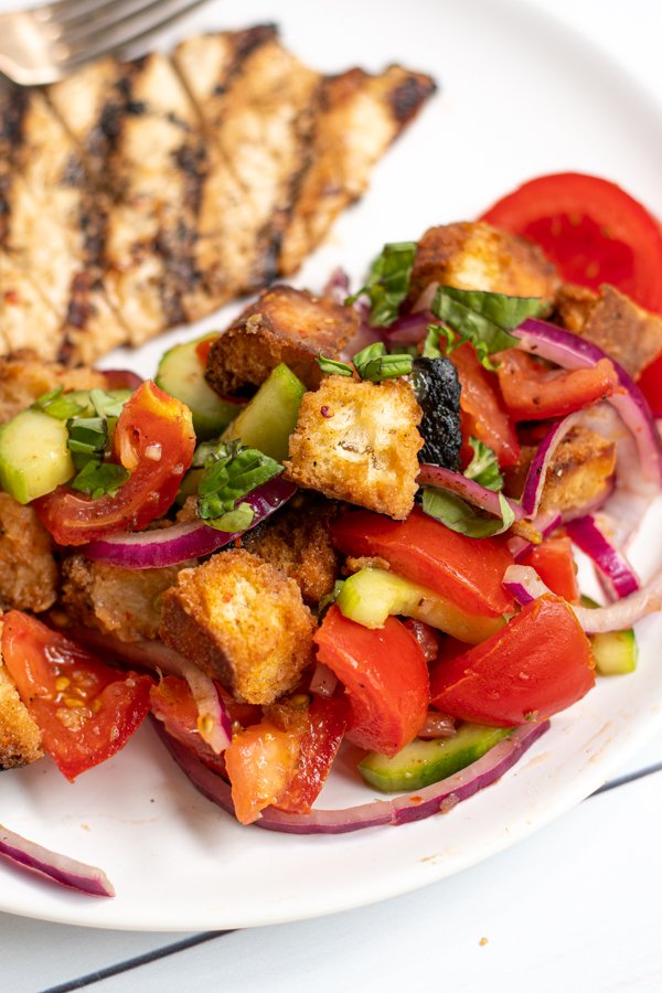close up of panzanella salad on a plate showing toasted bread cubes, tomatoes, cucumbers, and red onions
