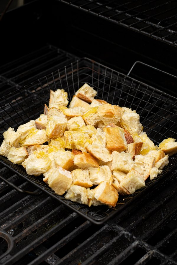 1 inch cubes of crusty bread in a grilling basket on the grill