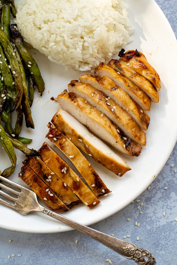 close up of a sliced up grilled chicken breast on a plate next to green beans and white rice