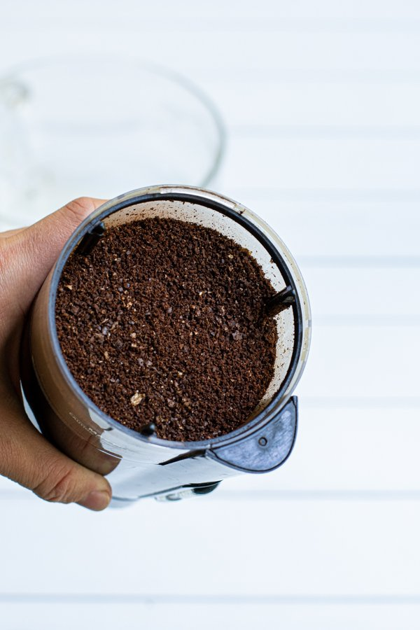 ground coffee in a small black coffee grinder
