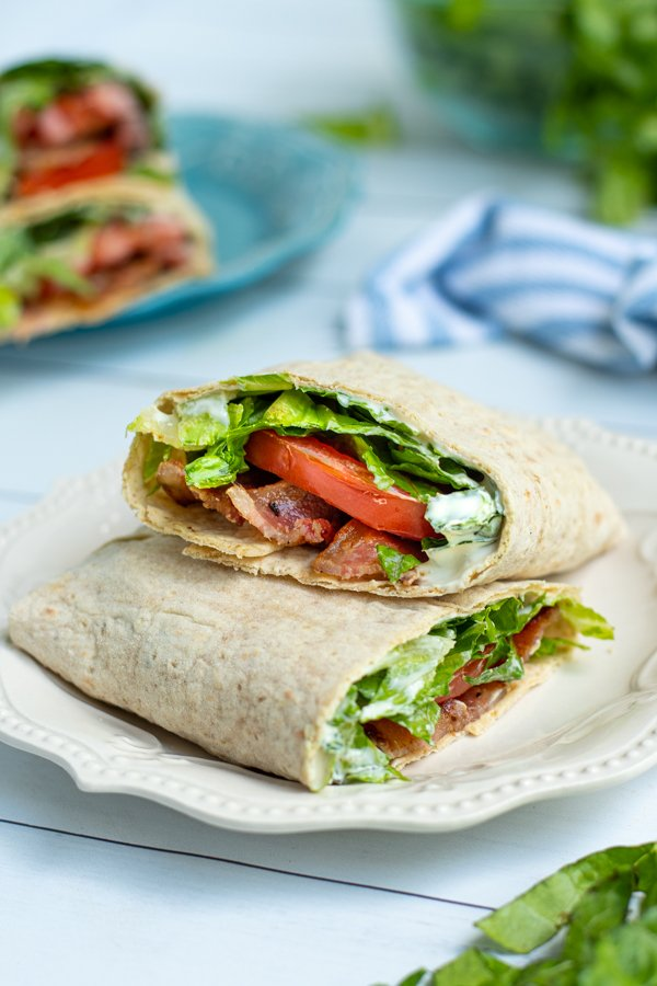 two halves of a BLT wrap on a white plate showing off the bacon, lettuce, tomato, and sauce on the inside