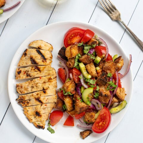 a white plate shot from overhead with sliced grilled chicken breast and a large serving of panzanella salad with tomatoes and grilled bread
