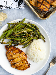 Overhead shot of a white plate with a teriyaki grilled chicken breast, grilled green beans with sauce, and white rice