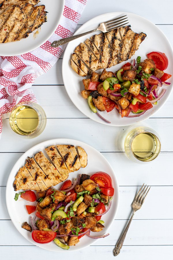 two plates with wine glasses and forks sitting on a white table with servings of grilled chicken breast and panzanella salad