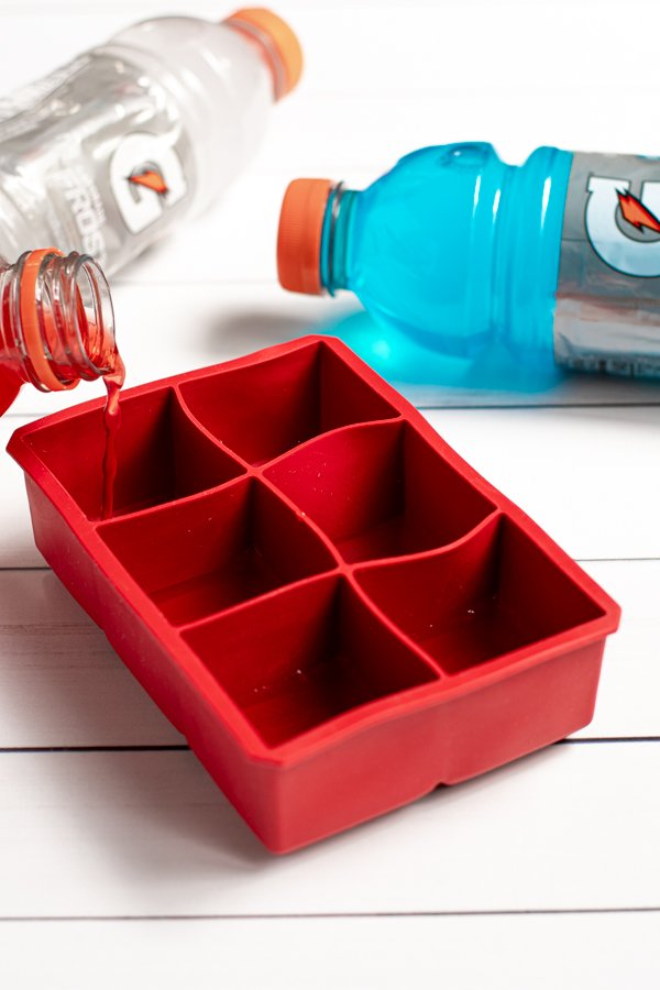 red gatorade being poured into a large red silicone ice cube tray