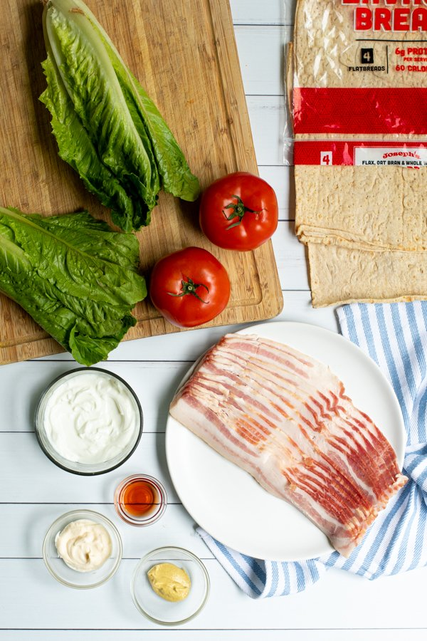 all of the ingredients needed to make BLT wraps lated out on plates and cutting boards