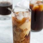 Pinterest Pin for How to make Cold Brew Coffee showing a glass of cold brew coffee swirled with freshly poured milk with ice and a straw