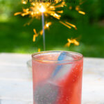 Pinterest Pin for red, white, and blue ice cubes showing a glass filled with red, white, and blue ice cubes on a table outside net to a sparkler