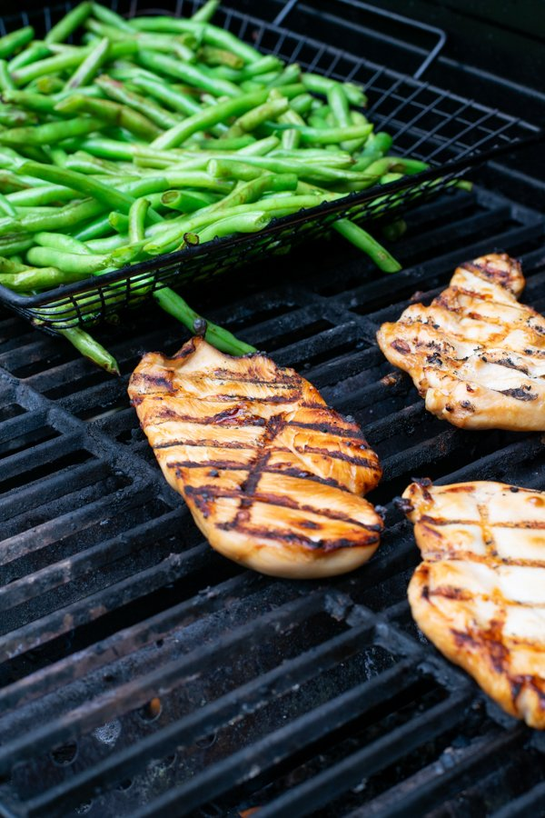 teriyaki marinated chicken breast on the grill next to a grill basket filled with fresh green beans
