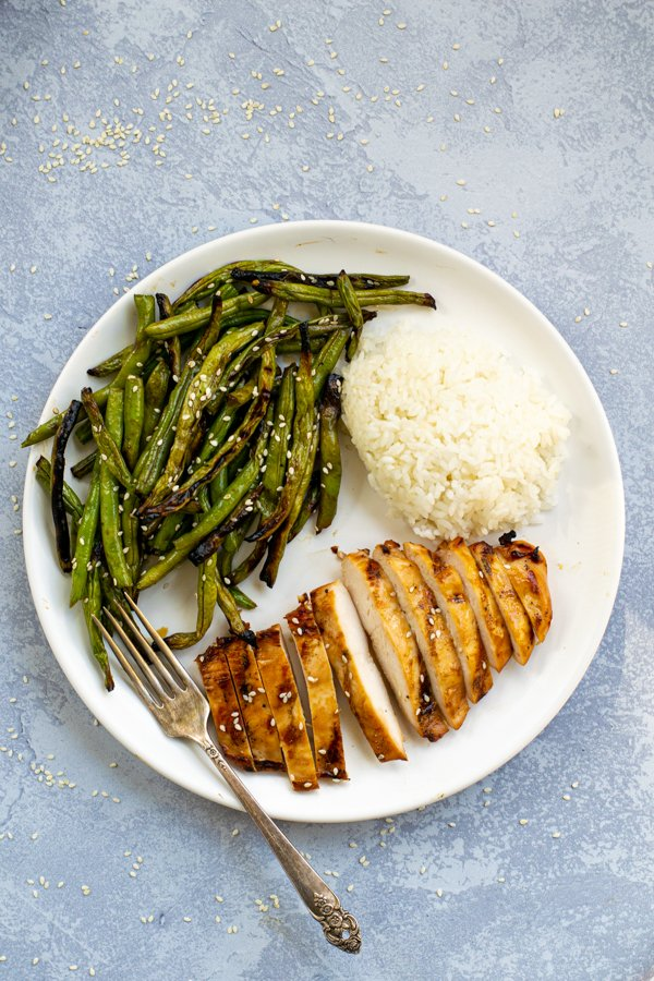 a white plate with teriyaki grilled chicken sliced up, grips grilled beans covered in sauce, and a pile of steamed white rice