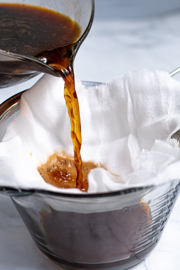Pouring coffee concentrate and the used coffee grounds into a cheese cloth to strain out the coffee grounds