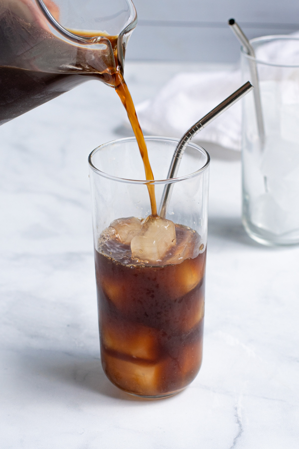 Pouring cold brew concentrate into a glass with ice cubes