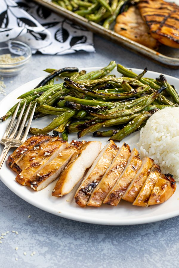 sliced grilled teriyaki chicken breast on a plate with crispy green beans and white rice