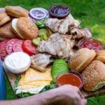 Pinterest Pin for Grilled Chicken Sandwich Board showing a man holding the large platter filled with chicken sandwich Ideas outside in the grass