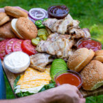 Pinterest Pin for Grilled Chicken Sandwich Board showing a man outside holding a large board filled with chicken sandwich toppings and chicken