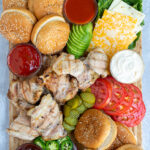 Pinterest Pin for Grilled Chicken Sandwich Board showing an overhead view of a large bamboo board containing grilled chicken, toppings, and buns