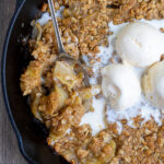 Grilled Apple Crisp Pinterest Pin showing the cooked dessert topped with ice cream and a spoon scooping some out