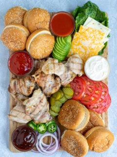 grilled chicken sandwich board filled with a variety of sauce, garnishes, buns, and grilled chicken