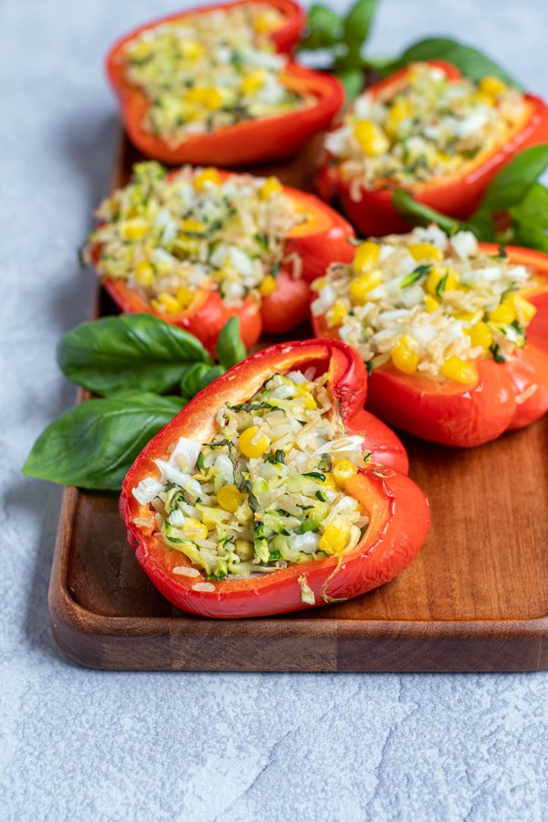 wood tray with grilled stuffed red bell peppers arranged next to fresh basil leaves