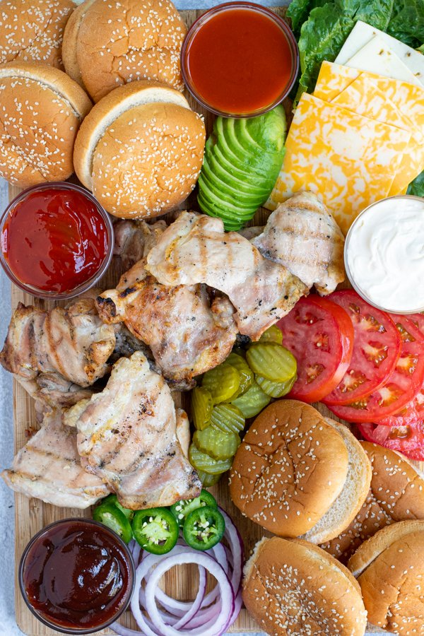 close up of grilled chicken on a large bamboo cutting board with different sandwich toppings around the chicken