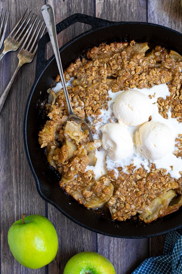 overhead shot of a cast iron on a table filled with apple crisp topped with ice cream and part of it scooped up with a spoon