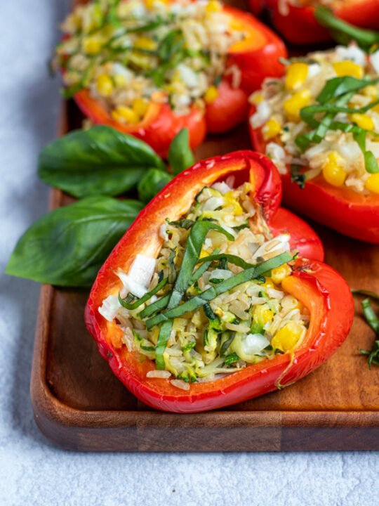 a close up of a grilled stuffed bell pepper topped with fresh basil leaves on a wooden serving tray