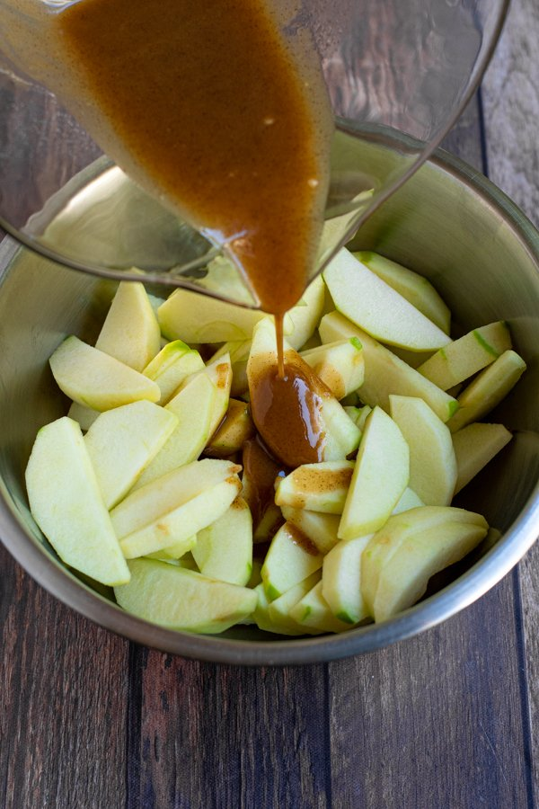 caramel colored filling being drizzled down over a bowl full of apple slices