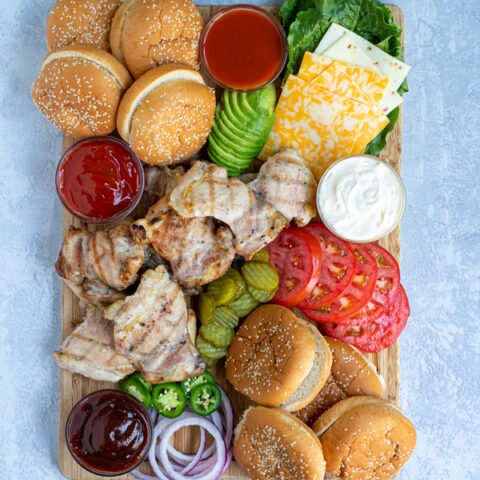 top view of a grilled chicken sandwich toppings board complete with grilled chicken, buns, and a variety of toppings