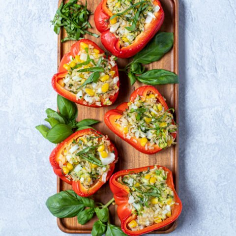 flatly of stuffed red bell peppers arranged on a wooden tray next to fresh basil leaves