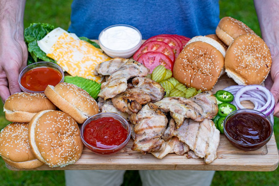 man holding a large bamboo board filled with grilled chicken, buns, and toppings