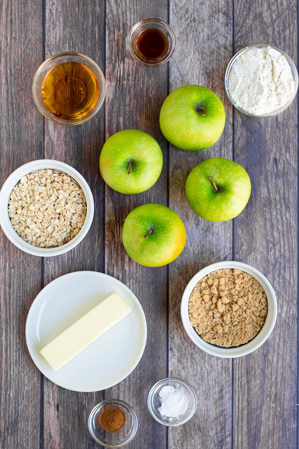 all of the ingredients need to make grilled apple crisp laid out on a table, like apples, flour, sugar, and oats