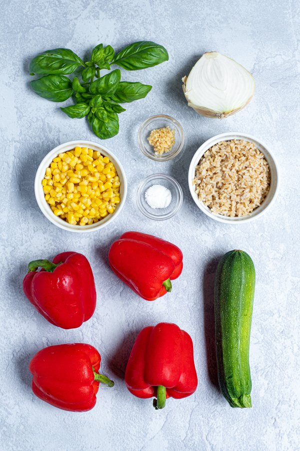ingredients needed to make stuffed bell peppers laid out on a table top
