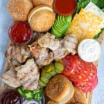 Pinterest Pin for Grilled Chicken Sandwich Board showing a large bamboo cutting board holing grilled chicken, sauces, and toppings