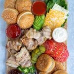 Pinterest Pin for Grilled Chicken Sandwich Board with an image of a board with grilled chicken, sauces, buns, and toppings