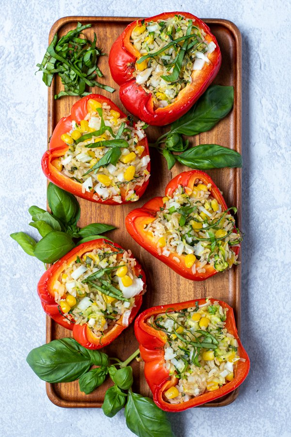 overhead view of a wooden platter of stuffed red bell peppers arranged next to basil leaves