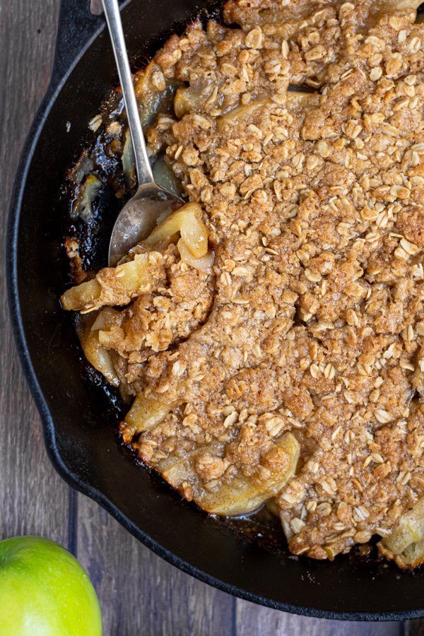 serving spoon in apple crisp in a cast iron skillet showing apples covered in the crisp oat topping