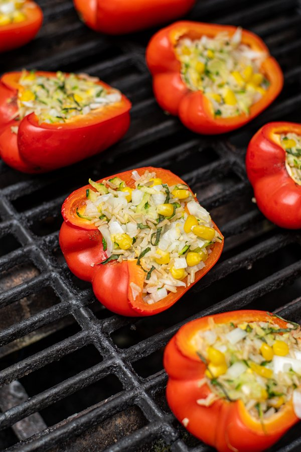 a stuffed red bell pepper on a grill grate
